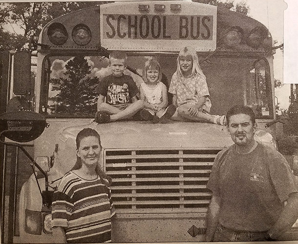 Mike and Jenny Aksamit standing next to one of their school buses with their three kids sitting on the hood of the bus
