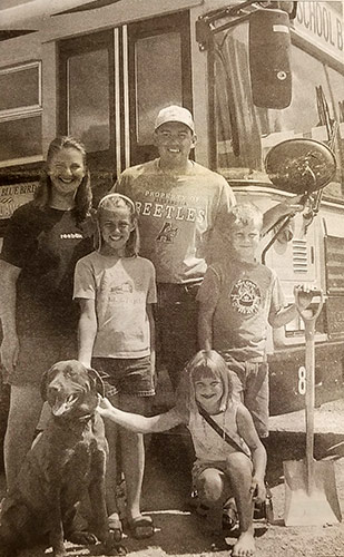 Mike and Jenny Aksmit with their three kids and family dog posing for a photo next to one of their school buses